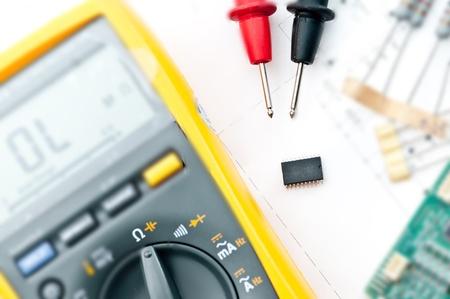 electricista: Comprobaci�n del circuito de Multi-Meter Ingeniero el�ctrico durante la comprobaci�n unidad de placa de circuito en un Multi-Merer