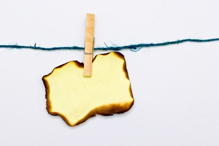 Hold Burn Paper with wood clip with white background Stock Photo - 17250687