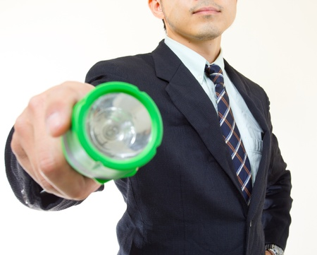 Businessman use flashlight for discovery something in the office photo