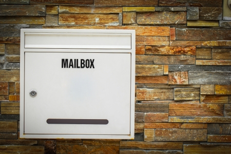 White mail box hang on the rock background photo