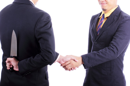 double cross: Businessmans shake hand after discussed while another people holding knife for double-cross