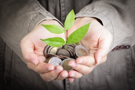 saving: Businessman cover growing plant with coin money