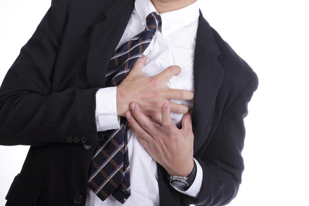Heart Attack ,Use hand grabbing a chest with white background Stock Photo