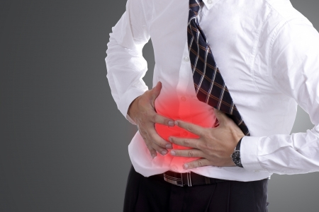 dolor abdominal: empresario sosteniendo el estómago para mostrar su dolor de estómago con el fondo blanco Foto de archivo