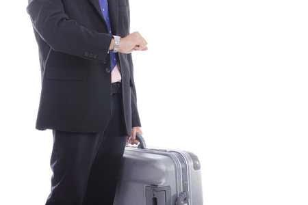 Businessman hold baggage and watch time for travel photo