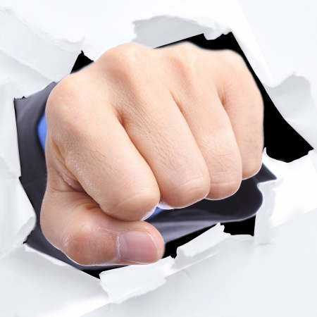 Businessman punch through white paper for slove every problem  photo