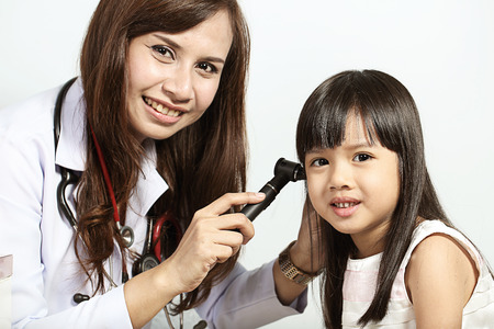 Doctor used Otoscope for examining Childs Ears in Clinic photo