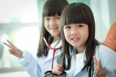 Two little girl kid doctor dressed with stethoscope photo