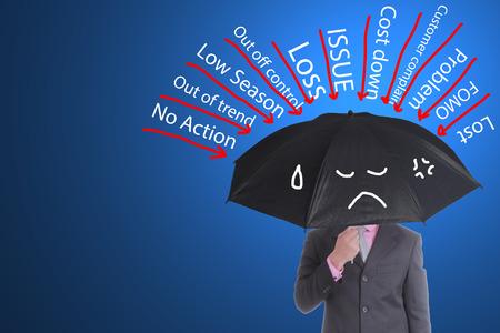 Businessman hold black color umbrella for prevent many problem in studio photo