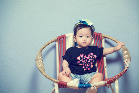Portrait lovely asian baby sit on vintage chair with blue background photo