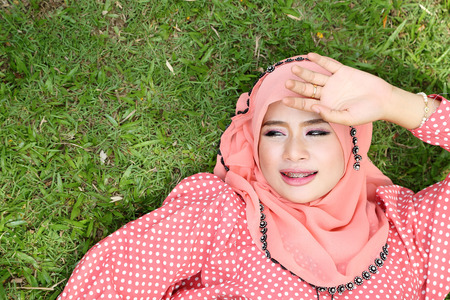 Lovely muslim girl lying on the natural grass. photo