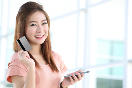 Portrait lovely girl type information with her  Credit card and  mobile phone  in Shopping mall photo