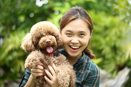 Asian girl hug with her poodle dog in the garden. photo