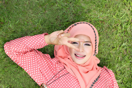 Lovely muslim girl lying on the natural grass photo