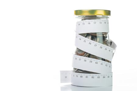 Rolling geld storten door meetlint voor bind je budget. Stockfoto