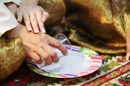 relatives: Thai Couple pour ceremonial water for dedicated to relatives in Wedding Ceremony