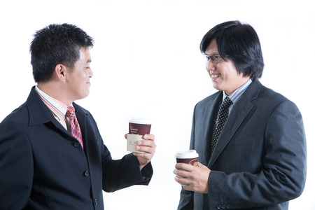 Two businessman holding paper coffee cup and discussing about their business on white background photo