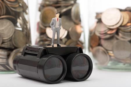 figura humana: Prism�ticos negros con figura humana aislada en frascos de monedas de fondo Foto de archivo