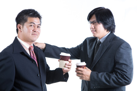 aisa: Two businessman holding paper coffee cup and discussing about their business on white background Stock Photo