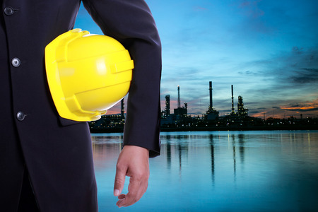cement chimney: Engineer stand in front of Petrochemical oil refinery plant for think to do something Stock Photo