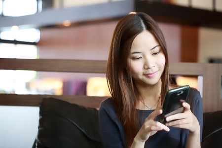 Young Asian girl use mobile phone for search information in coffee shop photo