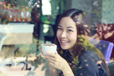 Young Asian women holding a cup of coffee with split tone beside mirror in cafe shop photo