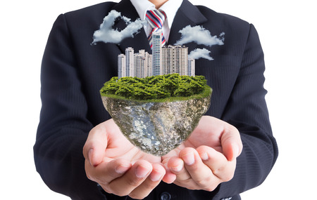 Businessman hold green city island with white background photo