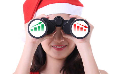 Christmas santa girl use binoculars for check graph up and down stock with white background photo