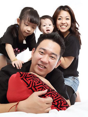 Asian Family portrait inside home with white background. photo