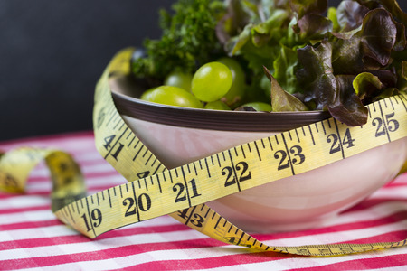Diet green salad and measuring tape slimming concept photo