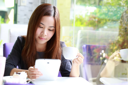 Young Asian women holding a cup of coffee beside mirror in cafe shop photo