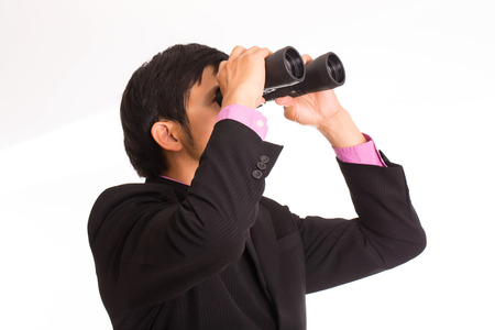 Businessman holding binoculars for search and check his business photo