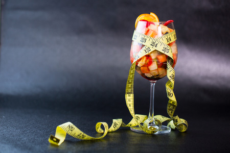 Diet fruit salad and measuring tape slimming concept photo