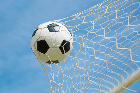 goal kick: Soccer ball in the goal after shooted in the game