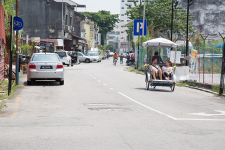 trishaw: GEORGE TOWN,PENANG ,MALAYSIA- CIRCA March 26, 2015: Traveler using Trishaw service to see George town art painting ,in Penang ,Malaysia.
