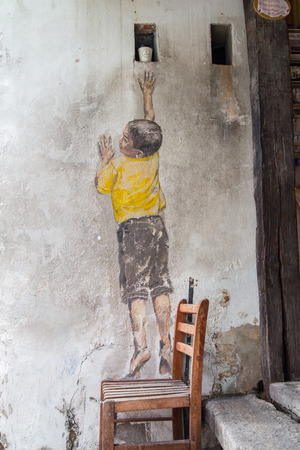 ernest: GEORGE TOWN,PENANG ,MALAYSIA- CIRCA March 26, 2015: Public street art Name Street Mural entitled Reaching Up on the wall by Ernest Zacharevic in Georgetown, Penang, Malaysia.