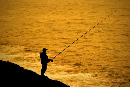 hombre pescando: Pescador pesca un perpon al lado del mar.