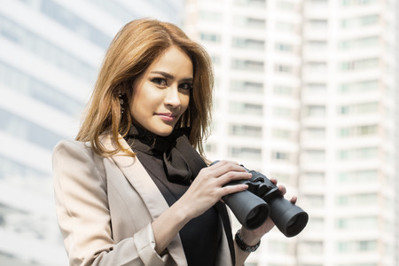 Businesswoman holding binoculars for search and check vision photo