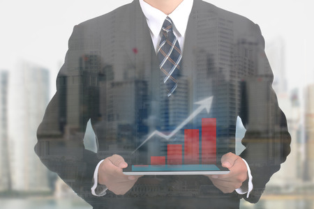 show case: Businessman holding touch pad for show case growing graph Stock Photo