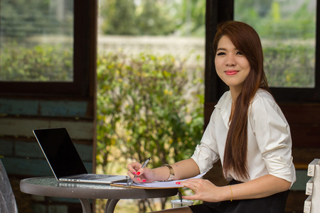 Young businesswoman sitting in coffee shop for check and search internet in the outside. photo
