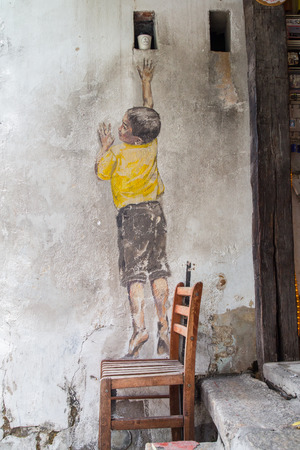 GEORGE TOWN,PENANG ,MALAYSIA- CIRCA March 26, 2015: Public street art Name Street Mural entitled Reaching Up on the wall by Ernest Zacharevic in Georgetown, Penang, Malaysia.