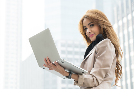 Businesswoman holding laptop for search and check information report