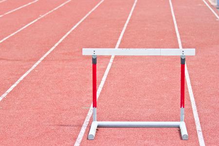 competitividad: obstáculos en la pista de atletismo rojo preparado para la competencia.