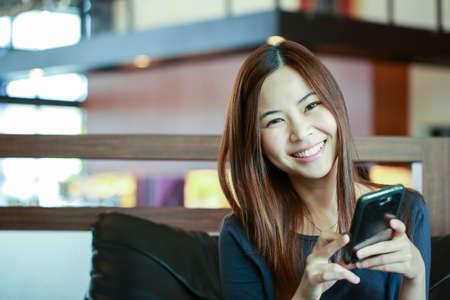 Junge asiatische Frauen benutzen Smartphone für Call und Massage zu ihrem Freund.