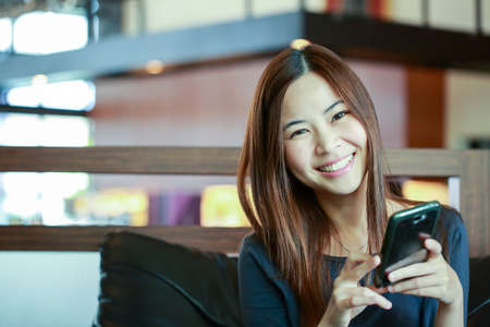 asian business: Young Asian women use smart phone for call and massage to her friend.