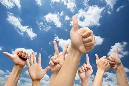 alzando la mano: La gente muestra las manos para acordar su oferta buena condicional con el cielo azul