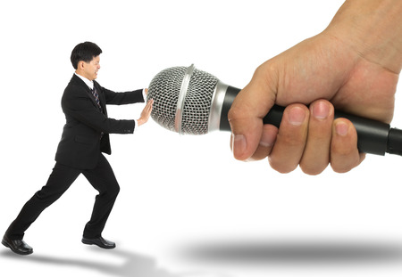 frighten: Business fear to speak and pusk microphone back ,no need to say. Stock Photo