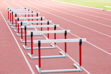 red competition: hurdles on the red running track prepared for competition Stock Photo