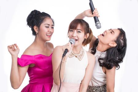 persona cantando: chica joven que sostiene el micrófono para cantar y alegría con la música en el fondo blanco.