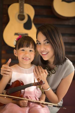 mam: Mam and daughter portrait with violin in studio school. Stock Photo